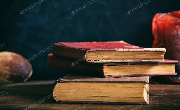Vintage books stack on black background
