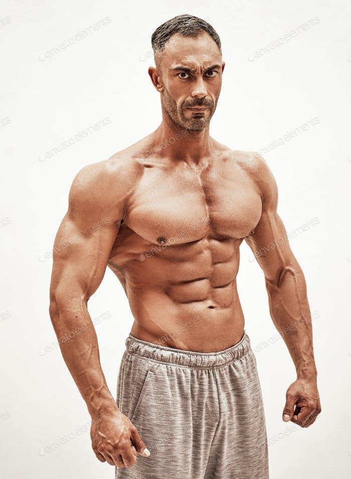 Shirtless sporty caucasian male isolated on a white concrete background showing chest muscles