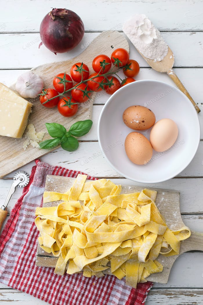 Homemade tagliatelle with ingradients for tomato sauce