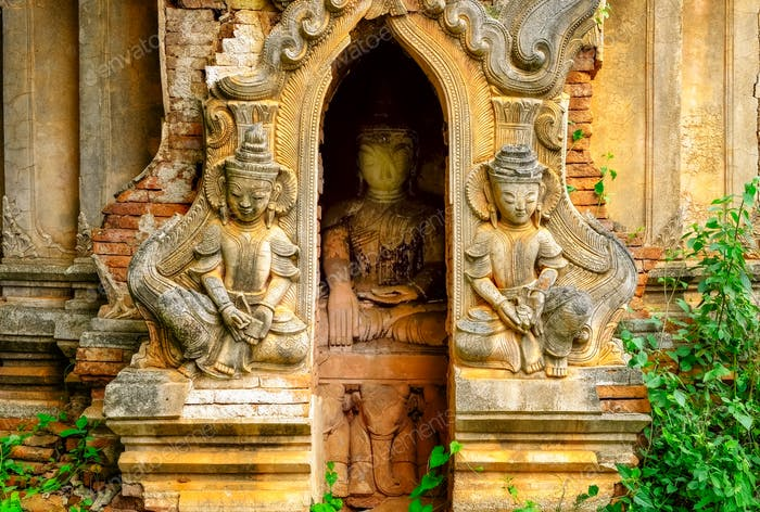 Detail of old stone temple ruins with statues, Myanmar