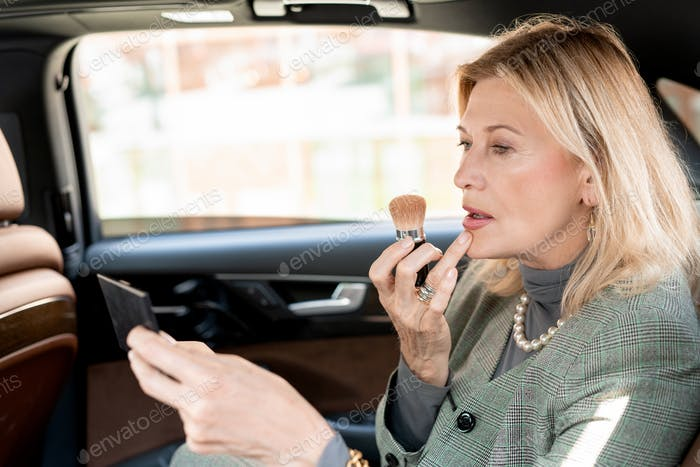 Mature blond businesswoman applying blush or powder on face in taxi cab