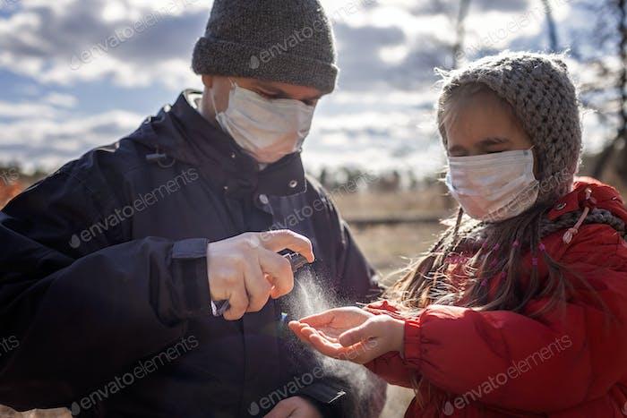 Vater und Tochter in Masken, die Alkohol Antibakterienspray auf die Hände auftragen, persönliche Hygiene