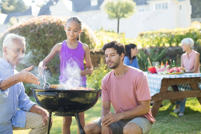 Father and grandfather watching while girl preparing barbecue