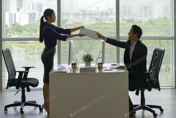 Female entrepreneur passing folder to coworker