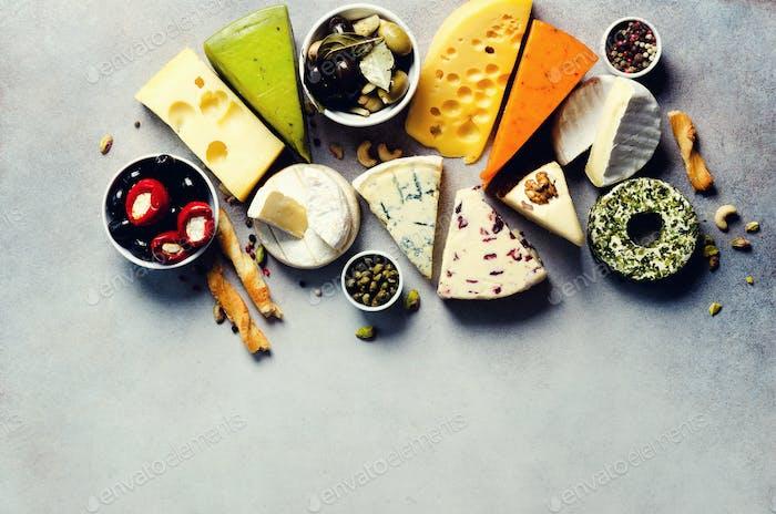 Sortiment von harten, halbweichen und weichen Käsesorten mit Oliven, Grissini Brotstäbchen, Kapern, Trauben, auf