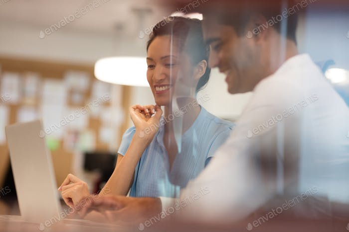 Happy business colleagues discussing while working in office
