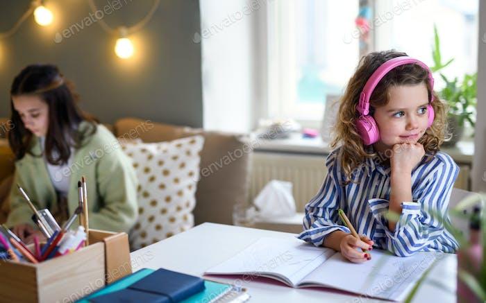 Sisters schoolgirls learning online indoors at home, coronavirus concept.