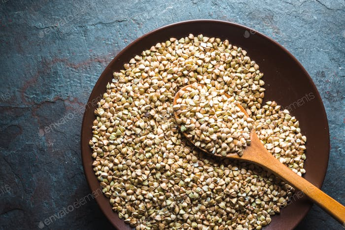 Wooden spoon in a plate with raw green buckwheat