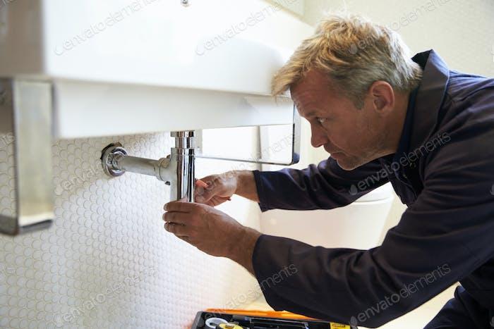 Klempner arbeiten auf Waschbecken im Bad