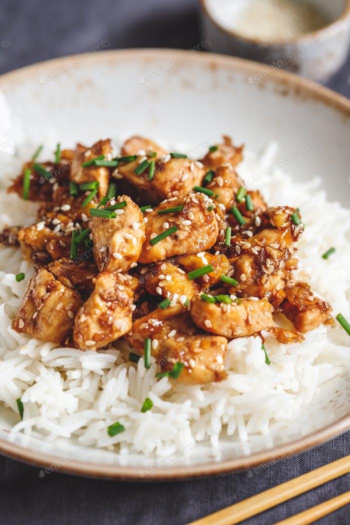 Sesamhühnerstücke mit weißem Reis serviert Frühlingszwiebeln. Traditionelles chinesisches Gericht.