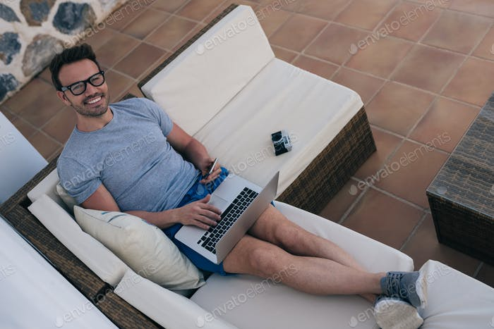 Man working from home at the yard on his computer