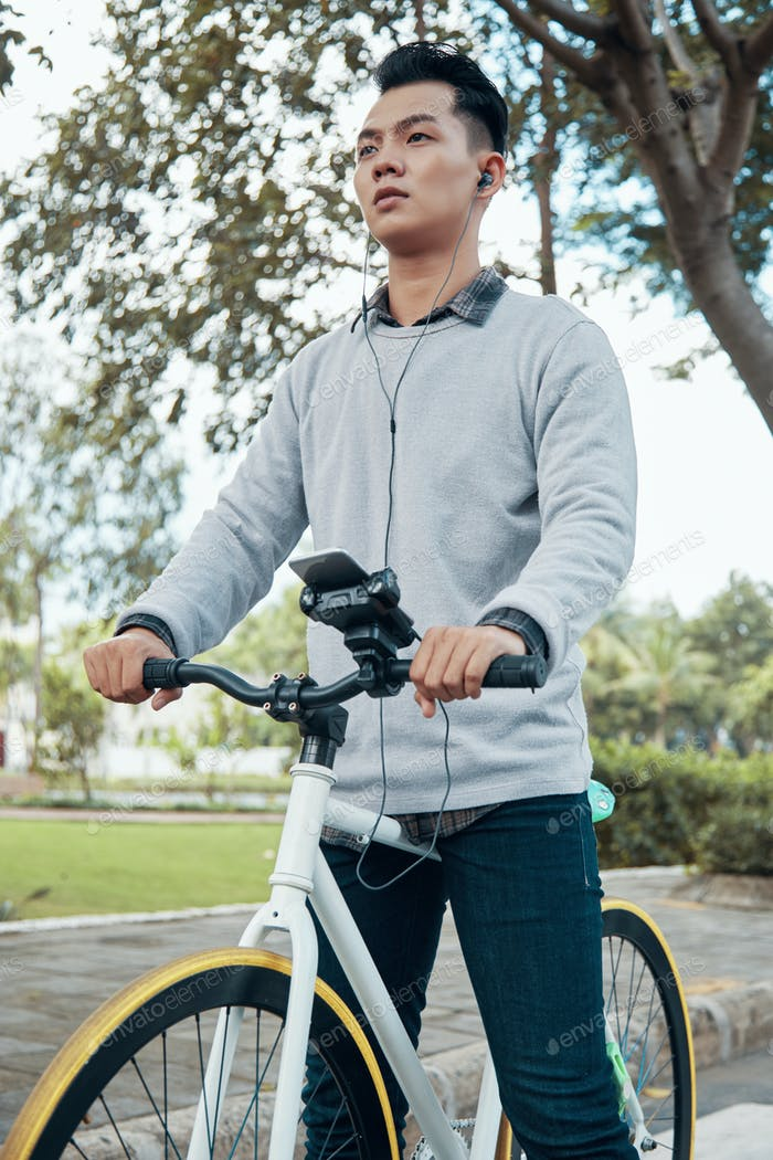 Asian guy with smartphone and earphones on bicycle