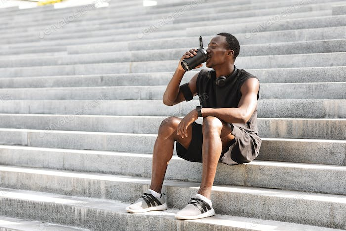 Thursty Black Male Athlete Drinking Water, Resting On Urban Stairs After Training Outdoors
