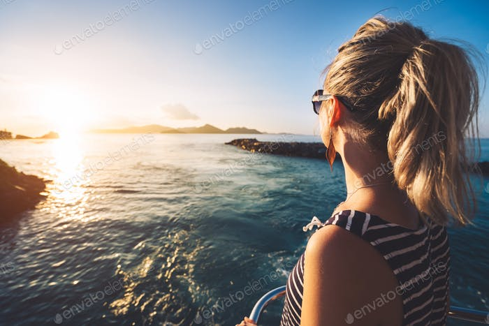Young adult women enjoying sunset over ocean from ferry boat, Seychelles island, La Digue