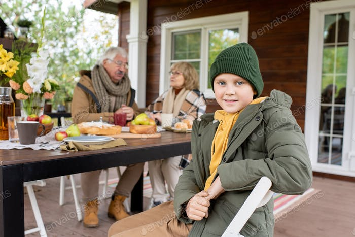 Happy schoolboy in beanie and warm jacket looking at you against grandparents