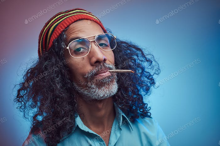 Studio portrait of African Rastafarian male smoking cigarettes