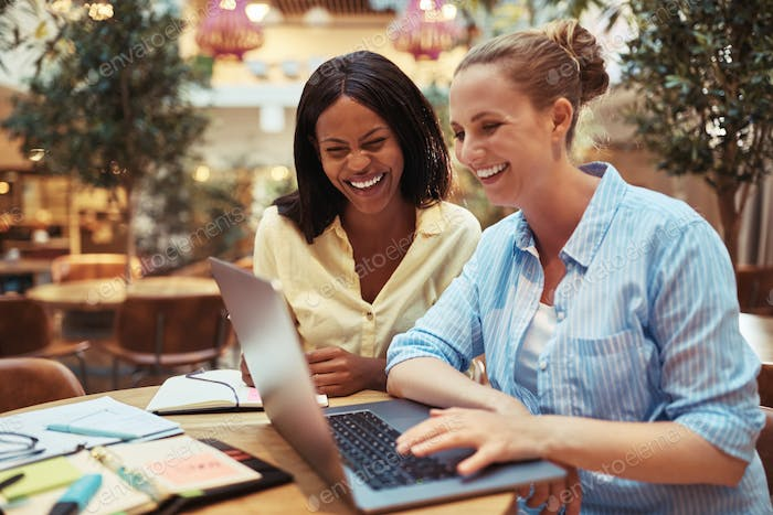 Diverse businesswomen laughing while working on a laptop