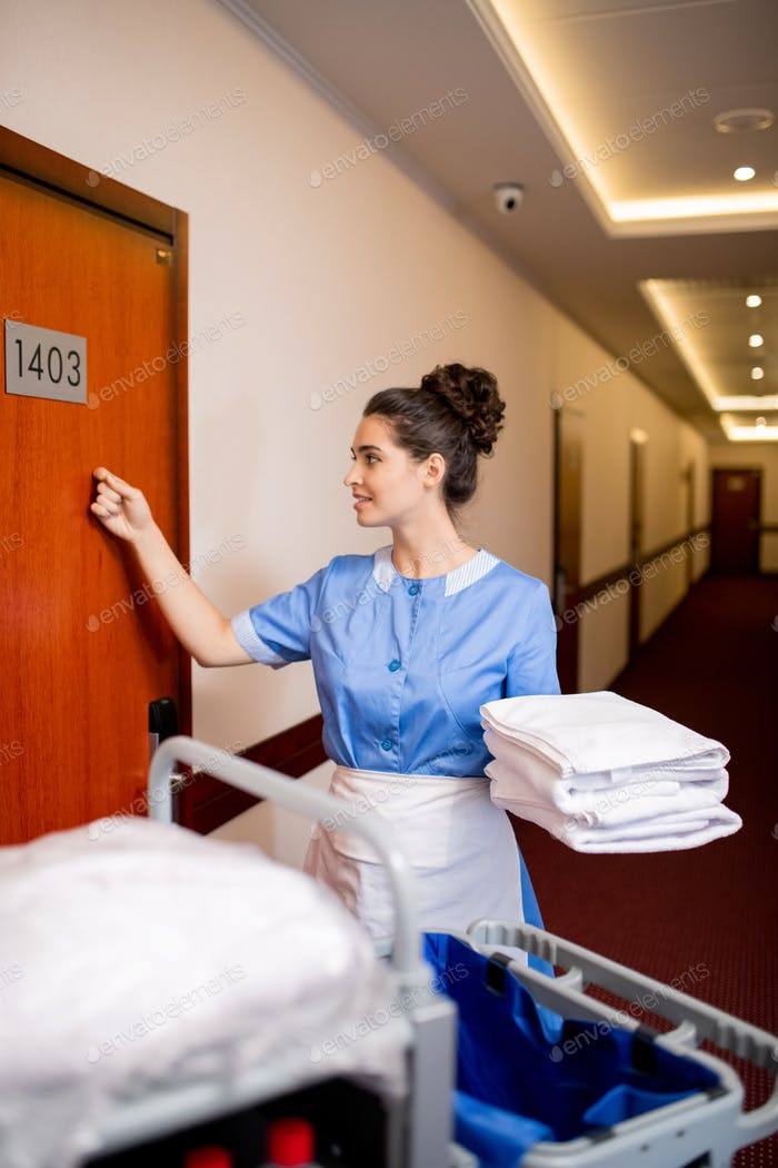 Pretty room maid in uniform holding clean towels while knocking on wooden door