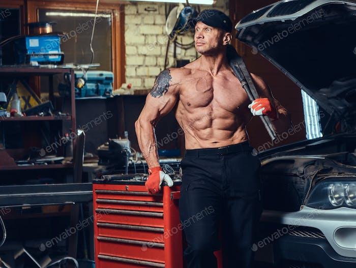 Shirtless mechanic in a garage.