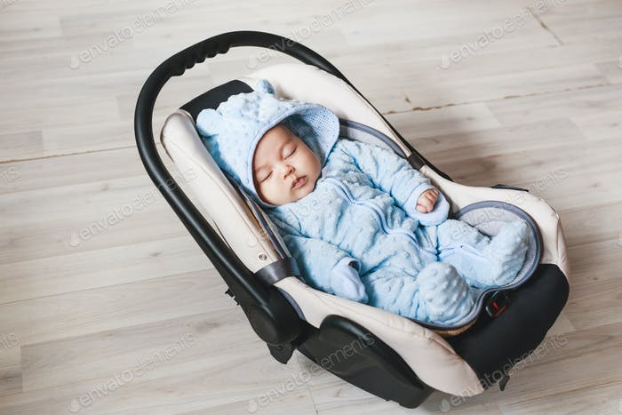 Portrait of cute mixed race baby boy sitting in car seat. Child transportation safety