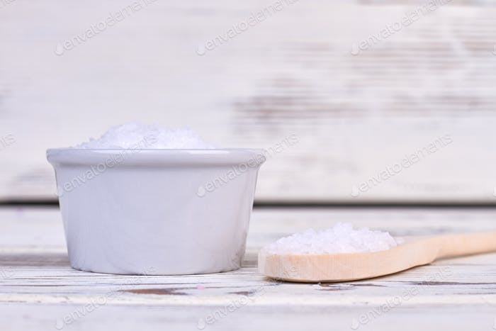 Pile of white salt with rustic wooden spoon.