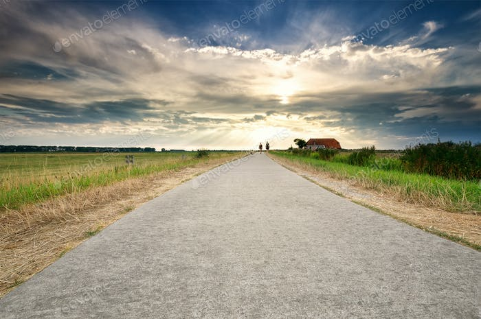 couple walking on path over dramatic sky
