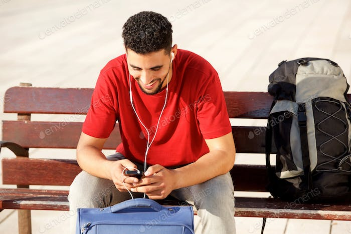 smiling young man sitting with bags and looking at mobile phone