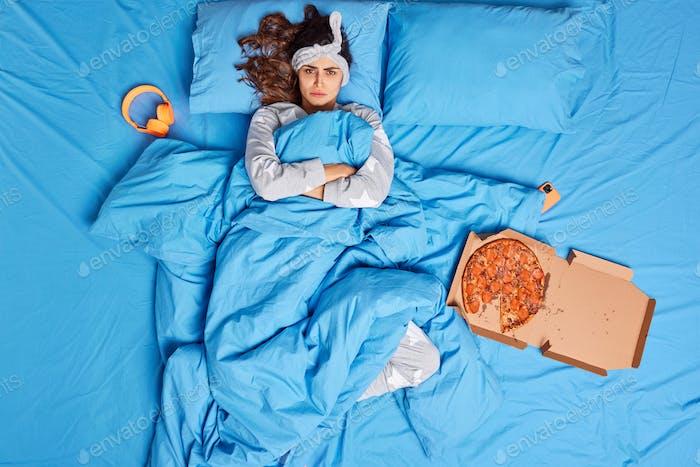 Unglücklich unzufrieden junge Frau hält die Arme verschränkt hat offensiven Ausdruck bleibt im bequemen Bett e