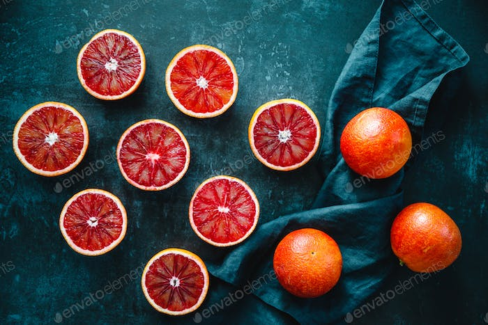 Flat lay food composition with cutted blood oranges on a dark blue background
