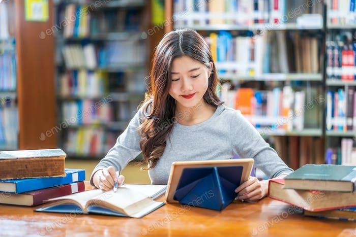 Asiático joven Estudiante en traje casual haciendo la tarea y el uso de la tecnología teblet