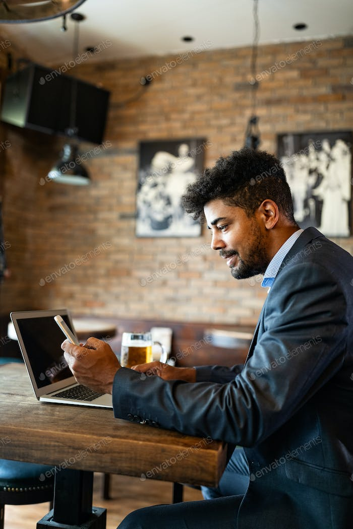 Handsome young business man, blogger or remote working with laptop in bar