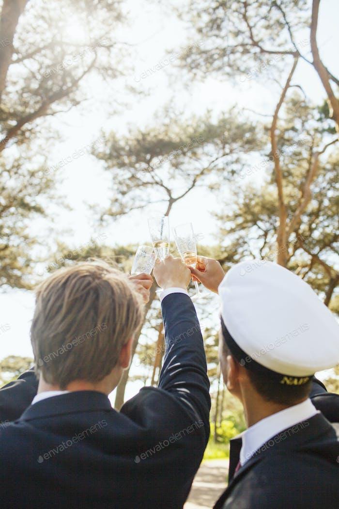 Male graduates toasting champagne flutes at university park