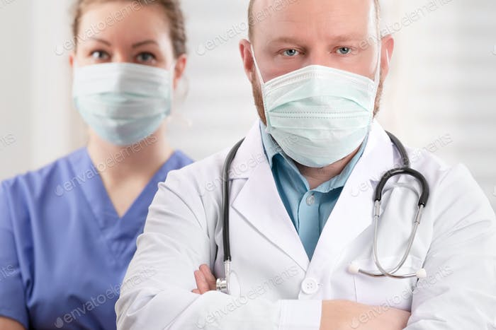 Confident Doctor And Nurse With Arms Crossed In Health Clinic or Hospital