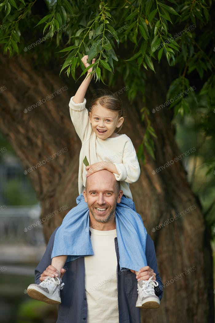 Cheerful Kid Riding on Fathers Shoulders