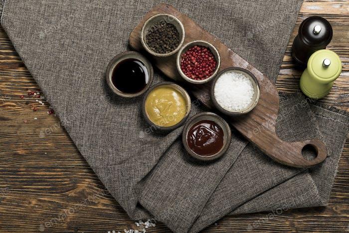 Verschiedene Gewürze, Kräuter, Knoblauch und Saucen auf hölzernem Hintergrund, Studiobeleuchtung, Draufsicht