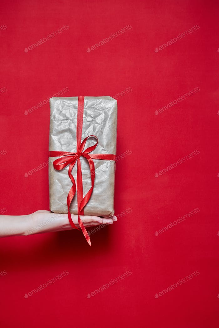 Womans Hand holding a box gift on red background