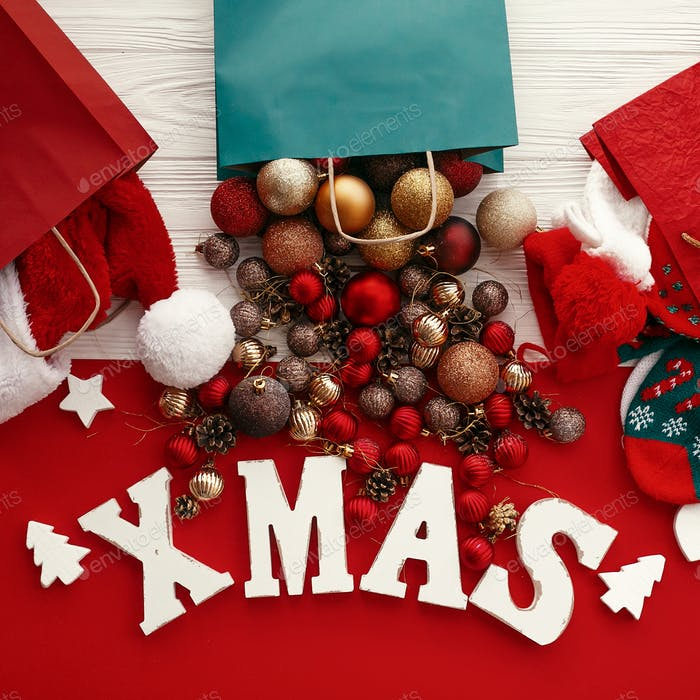 Xmas word with red and gold baubles from bag, santa hat and stockings in shopping bags
