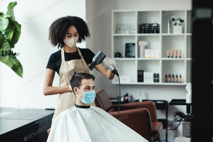 Black hairdresser making new hairstyle for client, both in protective masks