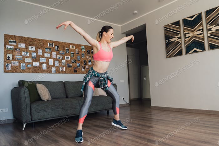 Smiling woman dancing in the middle of the living room enjoying herself and life
