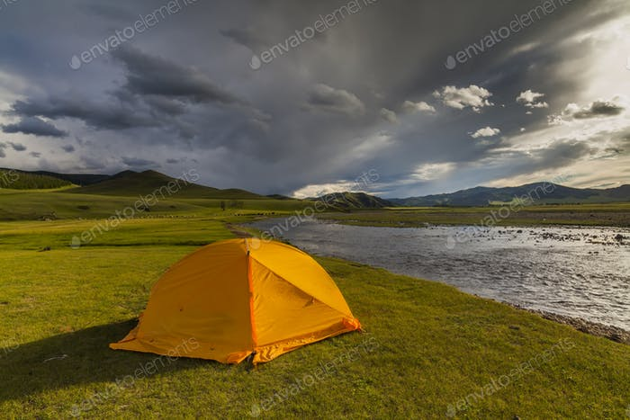 Orange tent on the river bank at sunset