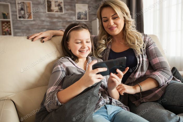 Little daughter with braces and her mother sitting on the couch