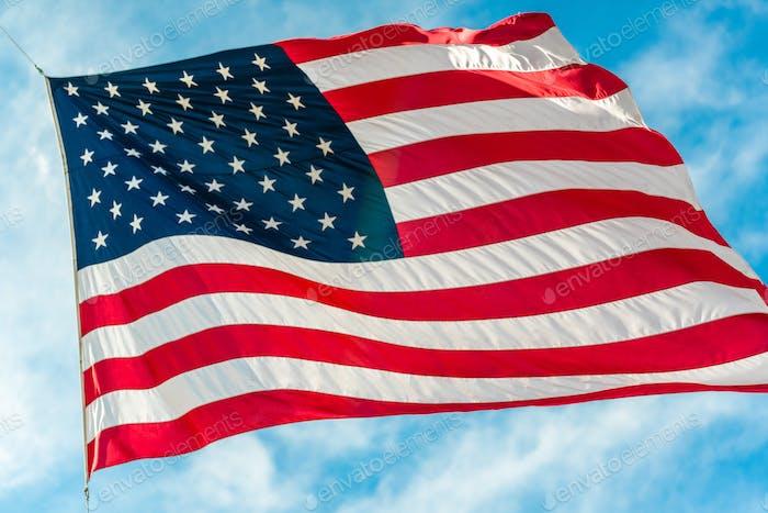 Amerikanische Flagge winkt in blau bewölkt Himmel