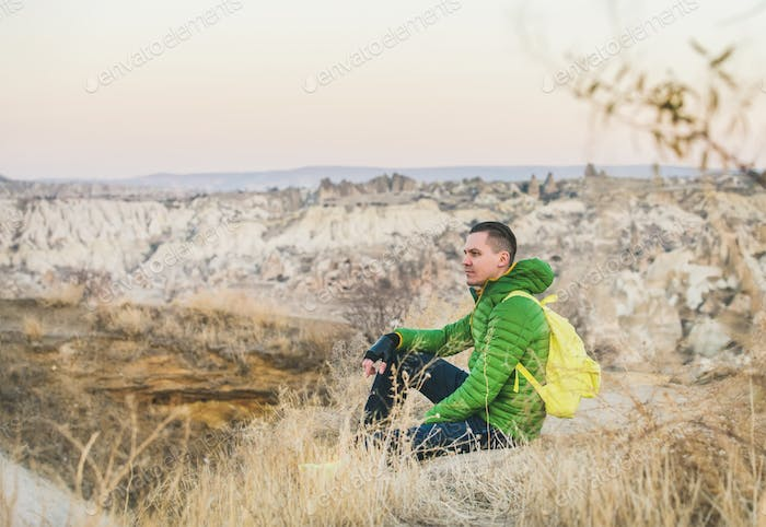 Young traveller sitting at edge of cliff, Cappadocia, Central Turkey