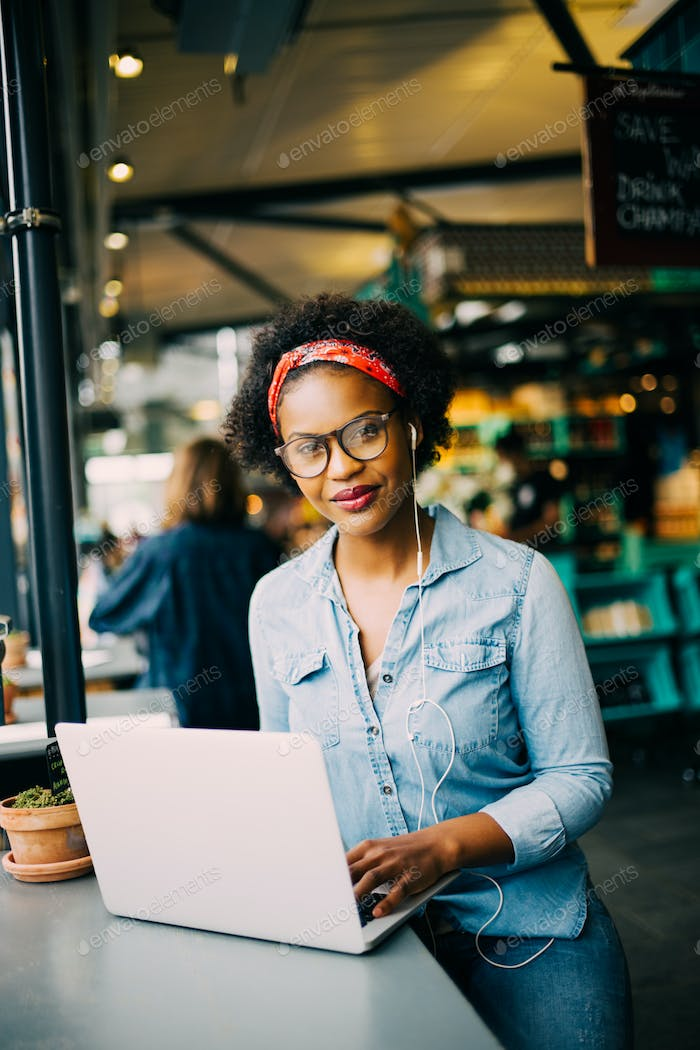 Smiling young African woman working online in a cafe