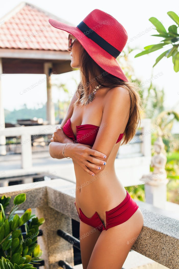 young woman with beautiful slim body wearing red bikini swimsuit