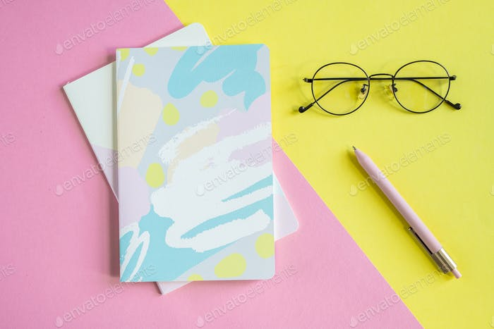 Eyeglasses and pen on yellow background and two notebooks on pink background