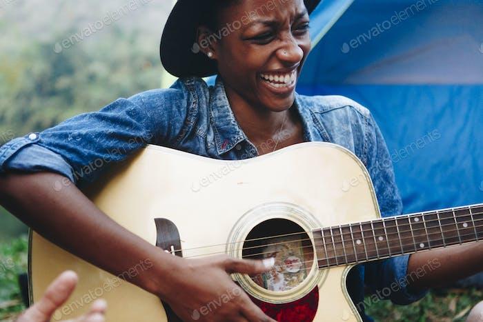 Afroamerikanerin spielt eine Gitarre auf einem Campingplatz