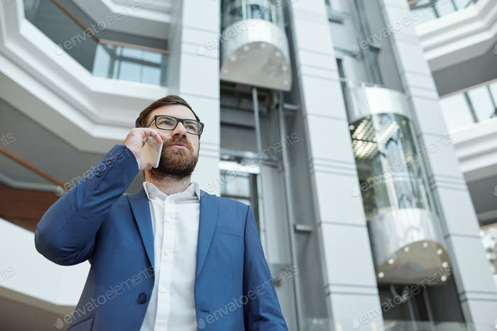 Young confident businessman with smartphone by ear consulting client