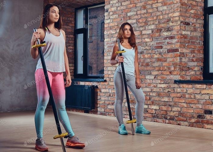 Frauen in Sportbekleidung halten eine Langhantel.