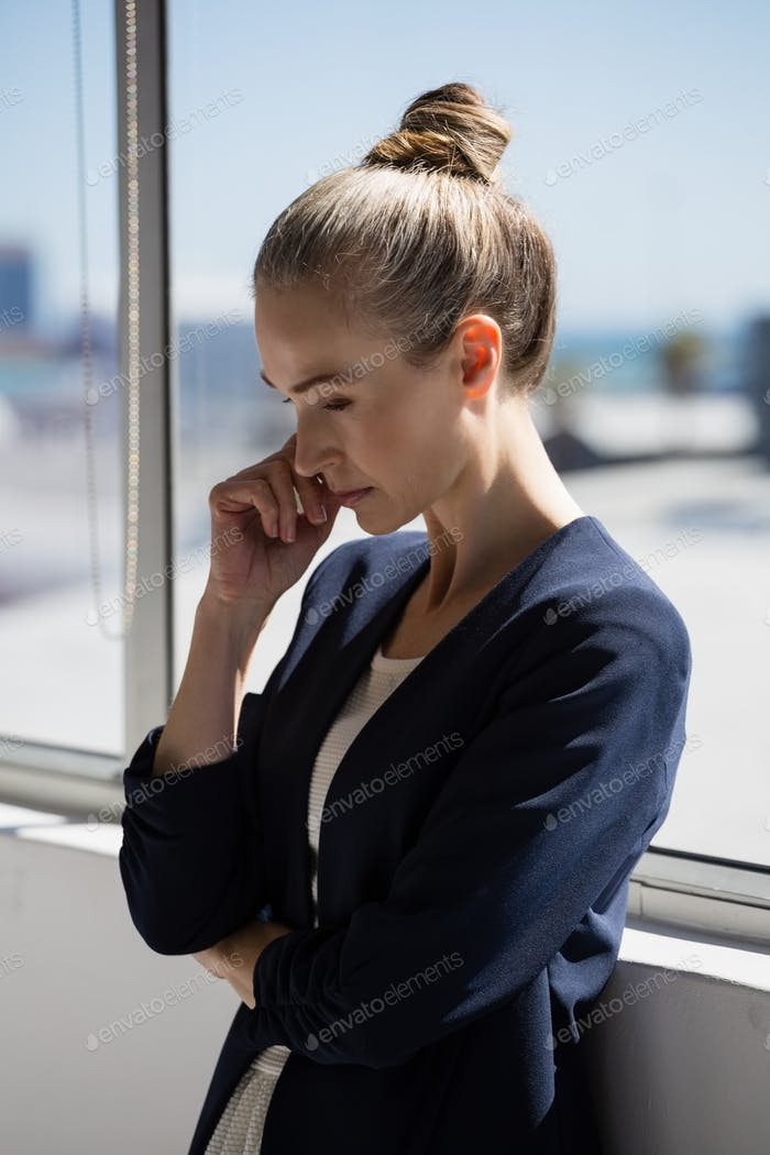 Thoughtful businesswoman looking lown while standing by window